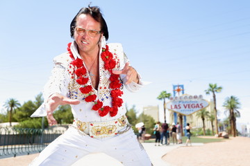 Elvis impersonator dancing by Las Vegas sign