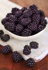 Sweet blackberry in bowl on wooden table