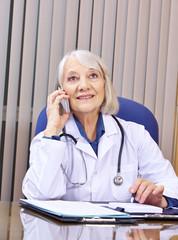 Ärztin telefoniert mit Smartphone