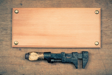 Sign board with old wrench hammer on wood wall background