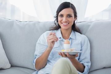 Cheerful brunette eating eggs