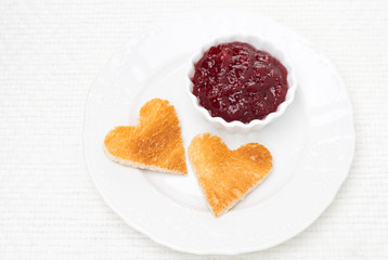 toasted bread in the shape of heart with berry jam