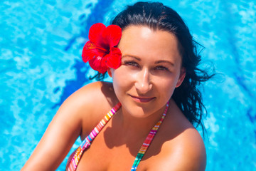 Beautiful brunette with red flower relaxing at swimming pool
