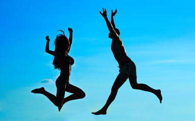 Silhouettes of jumping couple on blue sky background