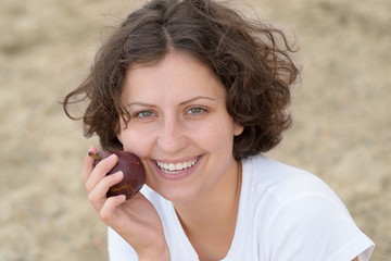 Natural young riant woman holding pear near mouth