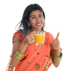 Thumb up Indian woman drinking orange juice