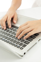 Female hands typing on laptop