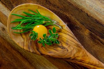 Drewniana łyżka z ziołami i żółtym pomidorem