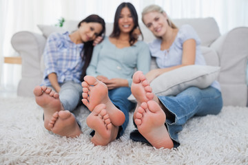 Friends relaxing on floor and smiling at the camera