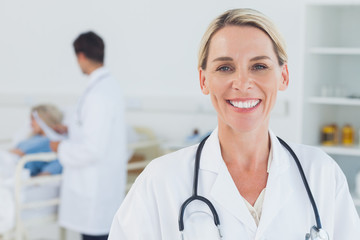Smiling blond doctor posing with doctor attending patient on bac
