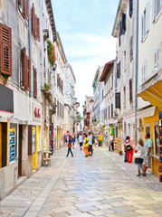 Wall Mural - People walk the old town streets in Porec, Croatia.