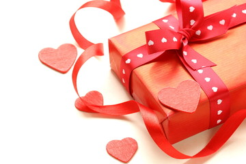 red gift box with ribbon and hearts on a white background