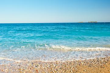 sea wave rolls on the sand and shingle beach at sunrise