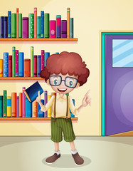 A smiling boy holding a book in front of the bookshelves