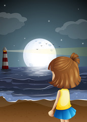 A small girl at the beach watching the lighthouse