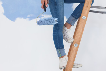 Woman holding paint roller on ladder
