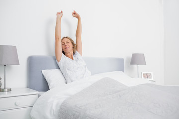 Blonde woman stretching her arms in bed in the morning
