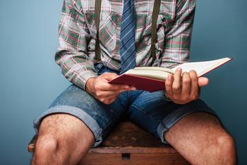 Man sitting on desk reading