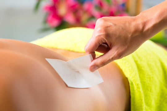 Man in Spa getting back waxed for hair removal