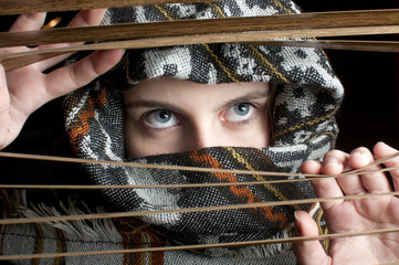 Portrait of young beautiful woman looking thrue window