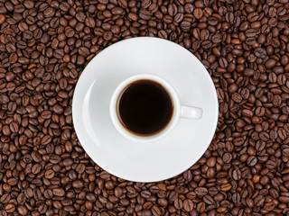 cup of coffee in coffee beans