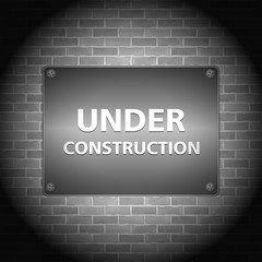 Under construction sign on brick wall