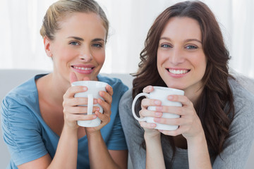 Friends having coffee and looking at camera