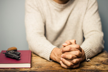 Praying man with a gun and important book
