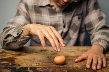 Man spinning an egg on the table