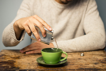Man adding alcohol to his coffee