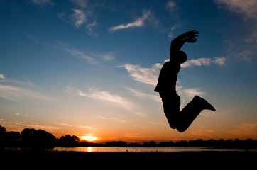 silhouette of a man jumping in the sunset
