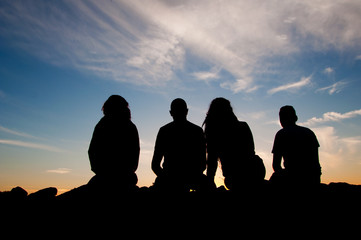 Young people silhouettes at sunset
