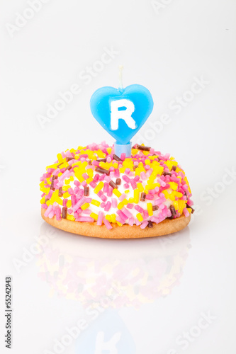 birthday cake with heart shaped candle with letter r