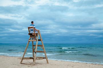 Man sitting on lifeguard chair