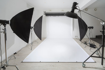 Photographic equipment and a white backdrop in studio.