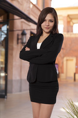 Pretty business woman stands with her arms crossed.