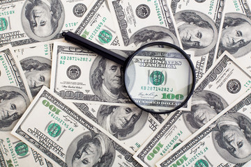 Dollars and black magnifying glass
