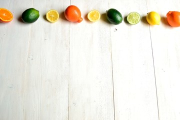 Colorful citrus fruits on white wood background