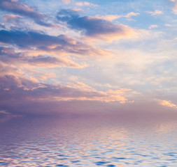 Foto op Plexiglas Lavendel Sunset with clouds reflected in water.