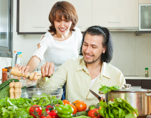 Friendly married couple preparing a meal of vegetables
