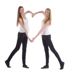 Young twins sisters making heart shape with arms on white