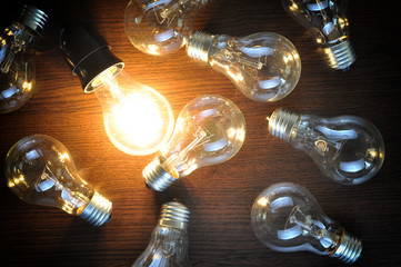 idea concept with glowing bulb on brown wooden background