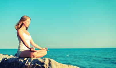 Fototapete - woman meditating in  lotus yoga on beach
