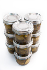 Nine jars of pickles stacked on a white isolated background