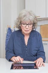Seniorin mit Brille und Tablet-PC in Küche