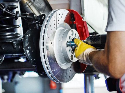 Car mechanic in a garage repairs a bracke