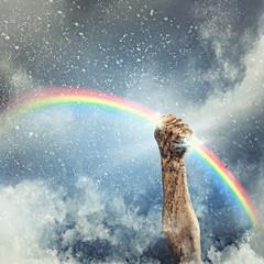 Human hand clenching rainbow