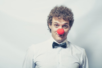 Young studen or Businessman with a red clown nose. Studio shot.