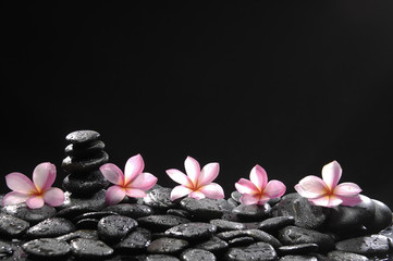 Fotobehang Spa spa concept with stacked stones with row of pink frangipani