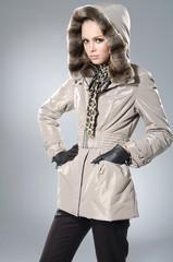 fashion model in coat clothes posing in studio